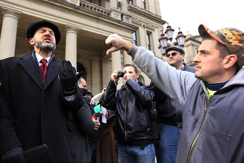 """David Dudenhoefer, left, a right to work supporter, receives a thumbs down sign from a union worker during a rally in Lansing, Mich., Thursday, Dec. 6, 2012. Tensions rose at the Capitol late Wednesday afternoon when hundreds of union members packed into the rotunda area, blowing whistles and shouting slogans such as """"Union buster"""" and """"Right to work has got to go."""" Senate Republicans introduced right-to-work legislation in the waning days of the legislative session as outnumbered Democrats pledged to resist the proposal and say rushing it through would poison the state's political atmosphere. (AP Photo/Carlos Osorio)"""