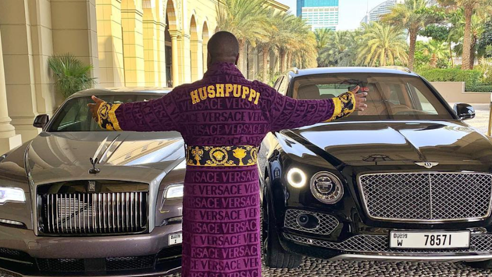 Hushpuppi in a monogrammed dressing gown by some luxurious cars