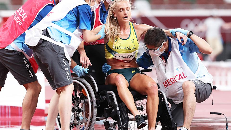Genevieve Gregson is helped into a wheelchair by officials after falling during the steeplechase at the Tokyo Olympics.
