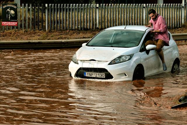 A man tries to get into a car stuck in floodwater in the town of Mandra.