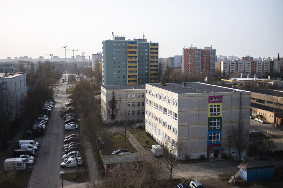 The headquarters building of the Arche, or Ark, an organization that supports children, youth and families, stand between residential buildings in the Hellersdorf neighbourhood, on the eastern outskirts of Berlin, Germany, Tuesday, Feb. 23, 2021. Since the outbreak of the coronavirus pandemic, the Arche has had to reduce their real face-to-face assistance or traditional classroom schooling as an offer for children, mainly from underprivileged families, drastically. Some kids are still allowed to come over in person, but only once every two weeks. (AP Photo/Markus Schreiber)