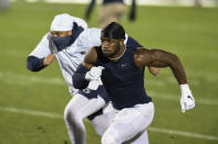FILE - Penn State defensive end Jayson Oweh warms up before an NCAA college football game against Ohio State in State College, Pa., in this Saturday, Oct. 31, 2020, file photo. Oweh is a possible first round pick in the NFL Draft, April 29-May 1, 2021, in Cleveland. (AP Photo/Barry Reeger, File)