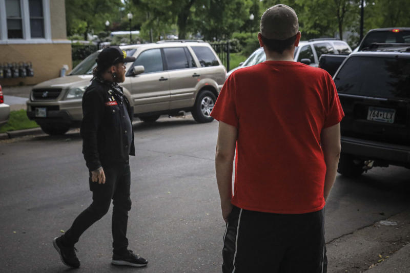 Michael Grunke, right, and his neighbor Obediah suspiciously checks a speeding pickup while on a neighborhood watch, which started after the death of George Floyd while in custody of police sparked unrest, Tuesday June 2, 2020, in Minneapolis, Minn. A week of civil unrest has led some Minneapolis residents near the epicenter of the violence to take steps to protect their homes and neighborhoods. (AP Photo/Bebeto Matthews)
