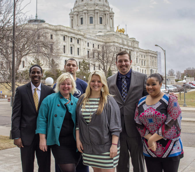 In this April 3, 2014 photo provided by Concordia University, from left: Akolade Gdadamosi; professor Jayne Jones; Chris Ploch; Hope Baker; Adam Goinz and Jordan Strickland pose for a photo outside the Minnesota State Capitol in St. Paul, Minn. Jones and the political science students said they became convinced by what they heard from lawmakers and police during their research for a political science project that some legislators had abused their state-issued immunity cards to get away with driving drunk. Their proposal to lift the privilege won committee approvals in 2012 but failed to get floor votes. So Jones said her class decided to try again this year and were taken by surprise when they learned they were getting a vote. (AP Photo/Concordia University, Melissa Wolf)