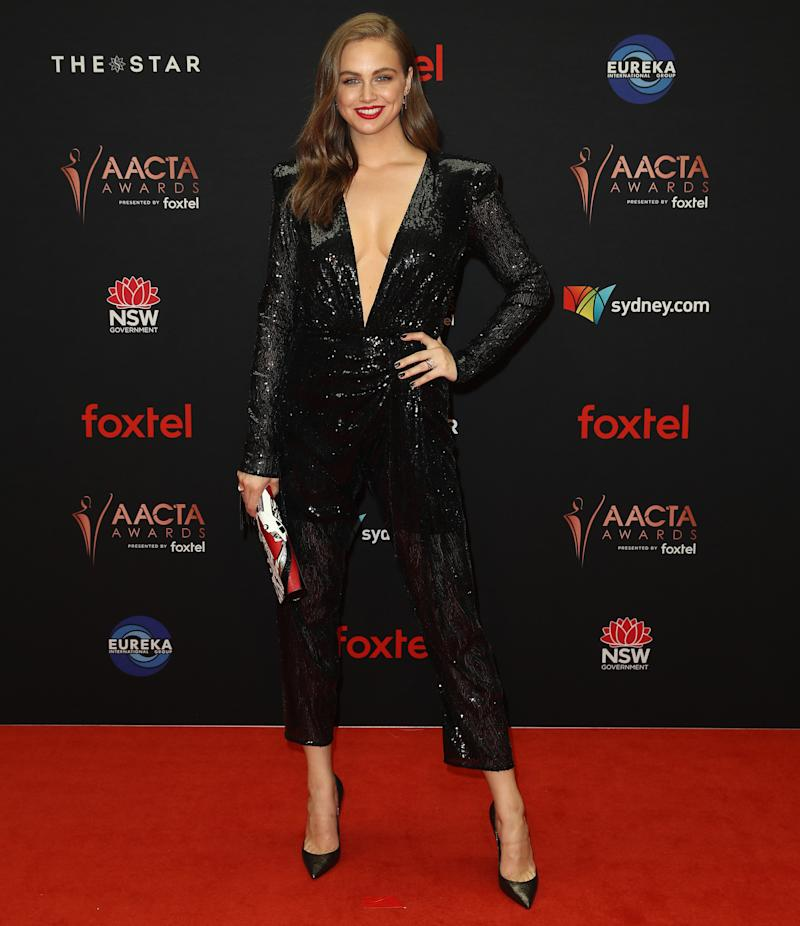 Ksenija Lukich dressed in a sequinned jumpsuit and stilettos on AACTAS red carpet