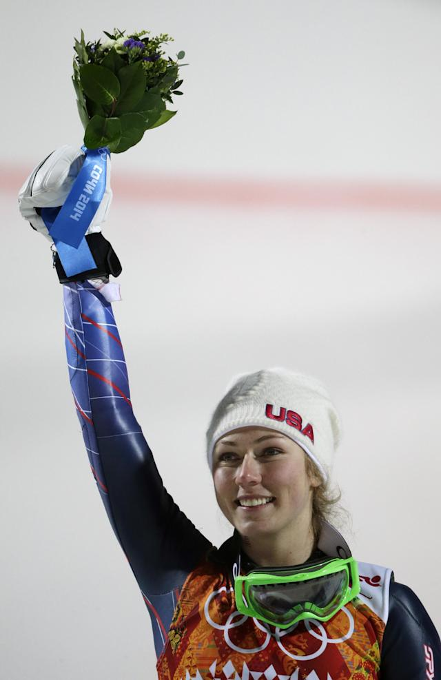 Women's slalom gold medal winner Mikaela Shiffrin of the United States holds up her bouquet at a flower ceremony at the Sochi 2014 Winter Olympics, Friday, Feb. 21, 2014, in Krasnaya Polyana, Russia.(AP Photo/Gero Breloer)