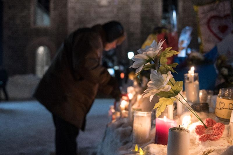 People place candles near a mosque that was the location of a shooting spree in Quebec City, Canada which left six people dead and eight wounded