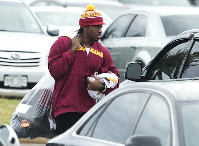 Washington Redskins quarterback Robert Griffin III walks to his car after cleaning out his locker at Redskins Park on Monday, Dec. 30, 2013, in Ashburn, Va. Redskins head coach Mike Shanahan was fired following a 3-13 season. (AP Photo/ Evan Vucci)