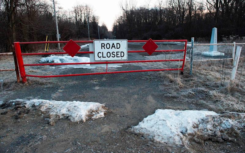 A closed gate and a boundary stone stand at the border crossing indicating the US/Canada border - Credit: Don Emmert/AFP