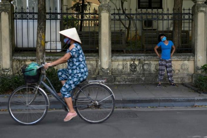 FILE PHOTO: A woman wears a protective mask as she exercises on the street amid COVID-19 pandemic, in Hanoi