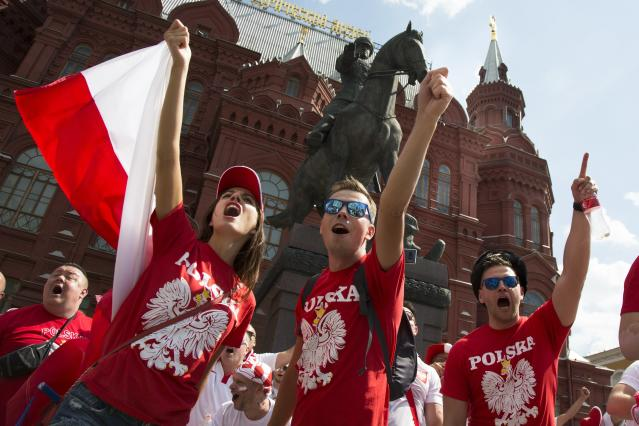 Polish soccer fans cheer in front of the the monument of Soviet Marshal Georgy Zhukov, near Red Square ahead of the group H match between Poland and Senegal during the 2018 soccer World Cup in Red Square in Moscow, Russia, Tuesday, June 19, 2018. (AP Photo/Alexander Zemlianichenko)