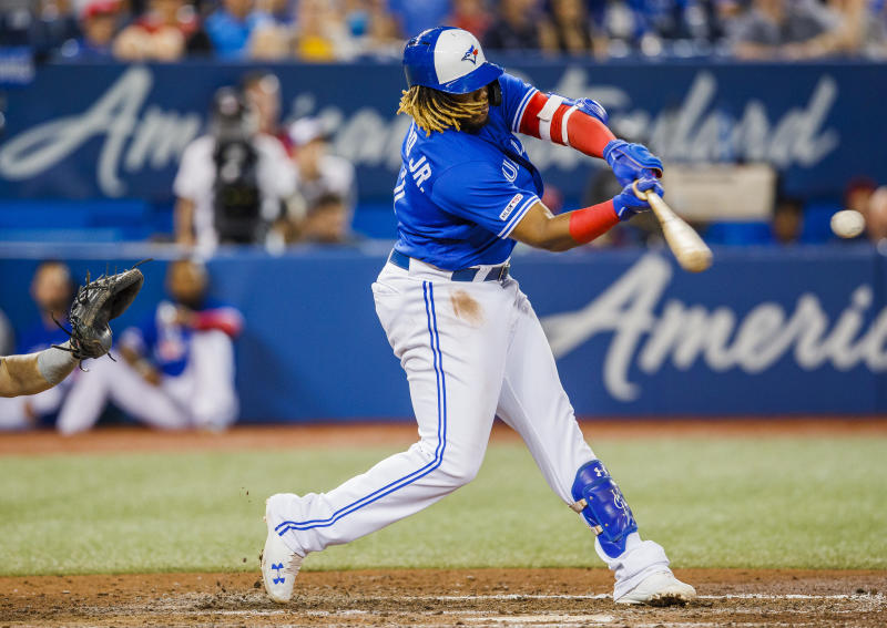 TORONTO, ONTARIO - JULY 27: Vladimir Guerrero Jr. #27 of the Toronto Blue Jays hits a double against the Tampa Bay Rays in the sixth inning during their MLB game at the Rogers Centre on July 27, 2019 in Toronto, Canada. (Photo by Mark Blinch/Getty Images)