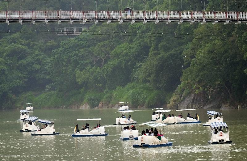 Tourists sail boats in Pitan, a popular area in Xindian district in New Taipei City on September 27, 2015 as typhoon Dujuan approaches the northeast of Taiwan (AFP Photo/Sam Yeh)
