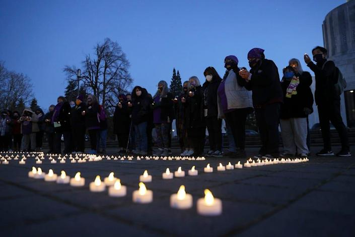 A crowd of mostly home care workers observes a moment of silence in front of the number of people that have died from COVID-19 in Oregon during a candle-lit vigil at the Oregon State Capitol on Thursday, March 25, 2021.