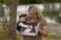 Aubrea Baker displays her wedding photo as she and her 7-month-old daughter Haylen visit one of her late husband's favorite fishing spots Saturday, Oct. 2, 2021, in Burlington, Kan. Her husband, Danny Baker, was among the 700,000 U.S. victims of COVID-19, dying on Sept. 14 after testing positive in July. (AP Photo/Charlie Riedel)