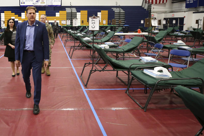 New Hampshire Gov. Chris Sununu, tours a makeshift medical facility on a basketball court in a gymnasium at Southern New Hampshire University in Manchester, N.H. (AP Photo/Charles Krupa)