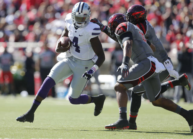 Kansas State's Daniel Sams(4) looks to get around Texas Tech's Keenon Ward (15) and Will Smith, right, during the first half of an NCAA college football game in Lubbock, Texas, Saturday, Nov. 9, 2013. (AP Photo/Lubbock Avalanche-Journal,Stephen Spillman)