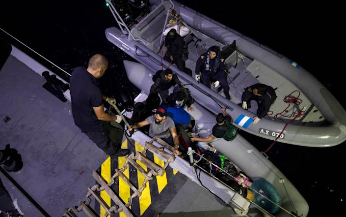Refugees and migrants board a Greek coast guard ship during a rescue operation in September 2019 near the Greek island of Samos - Petros Giannakouris/AP