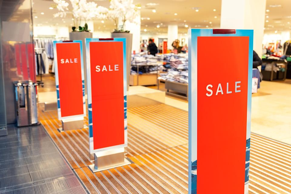 Red bright sale banner on anti-thieft gate sensor at retail shopping mall entrance.
