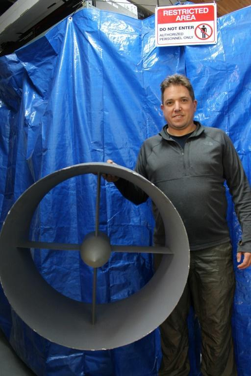 NFT co-founder Guy Kaplinsky poses with a model propeller before a curtain concealing work the startup is doing on a flying car in the Silicon Valley city of Mountain View, with a presentation expected at the Consumer Electronics Show in Las Vegas