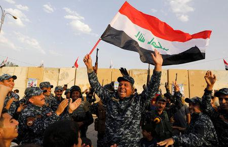 FILE PHOTO: A member of Iraqi Federal Police waves an Iraqi flag as they celebrate victory of military operations against the Islamic State militants in West Mosul
