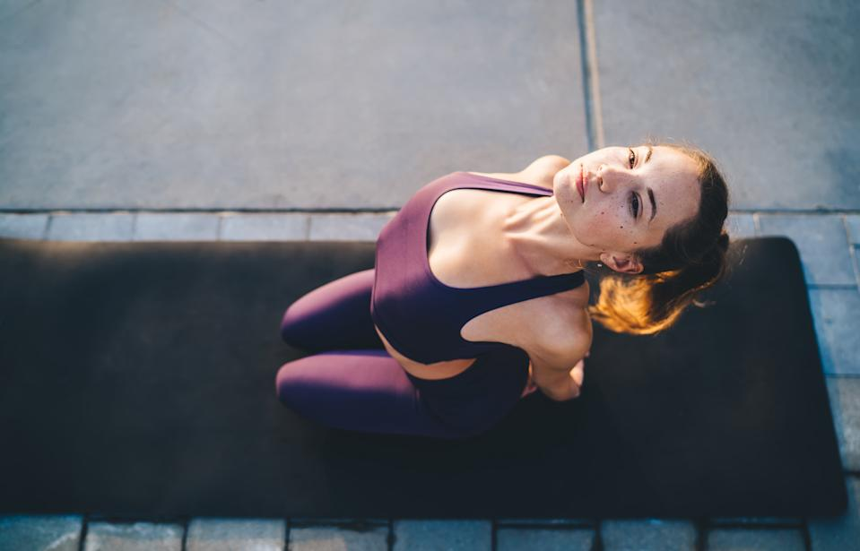 From above of focused young woman sitting on rug in Hero pose and stretching while training yoga exercise on concrete floor at daytime