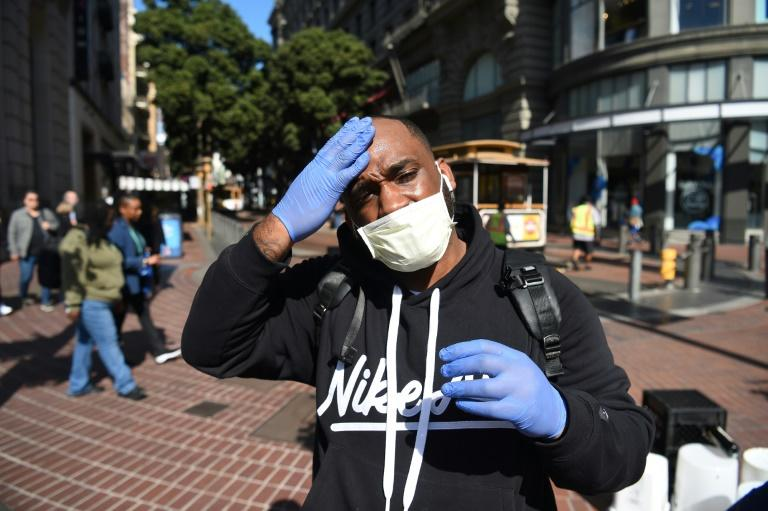 A man adjusts his mask and gloves, a precaution to protect himself from coronavirus, while walking by cable car in San Francisco, California