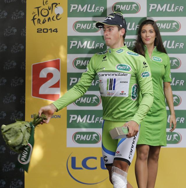 Peter Sagan of Slovakia, wearing the best sprinter's green jersey, thaws his flowers to fans on the podium of the seventh stage of the Tour de France cycling race over 234.5 kilometers (145.7 miles) with start in Epernay and finish in Nancy, France, Friday, July 11, 2014. (AP Photo/Christophe Ena)