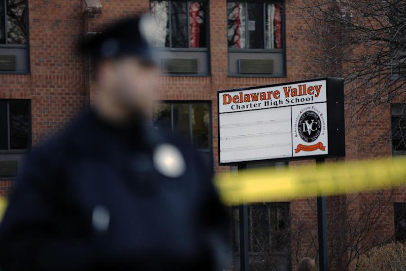 A police stands by caution tape at the Delaware Valley Charter School Friday, Jan. 17, 2014, in Philadelphia. Police say two students have been shot at the Philadelphia high school. (AP Photo/Matt Rourke)