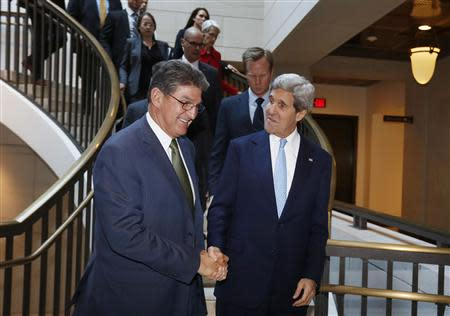 U.S. Secretary of State Kerry shakes hands with U.S. Senator Manchin as they arrive on Capitol Hill before Kerry briefs members of the Senate Banking Committee behind closed doors about Iran and his recent negotiations in Europe, in Washington