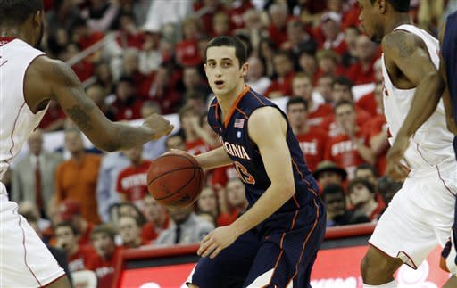 Virginia's guard Sammy Zeglinski (13) tries to squeeze between North Carolina State's Richard Howell and Lorenzo Brown during the second half of an NCAA college basketball game in Raleigh, N.C., Saturday, Jan. 28, 2012. Virginia won 61-60. (AP Photo/Jim R. Bounds)