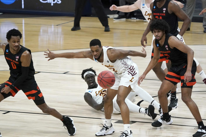 Loyola Chicago guard Marquise Kennedy (12) fights for a loose ball with Oregon State guard Gianni Hunt (0) and guard Ethan Thompson, right, during the first half of a Sweet 16 game in the NCAA men's college basketball tournament at Bankers Life Fieldhouse, Saturday, March 27, 2021, in Indianapolis. (AP Photo/Jeff Roberson)