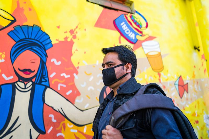 A man wearing a facemask as a preventive measure against the COVID-19 novel coronavirus walks along a market area in New Delhi on March 17, 2020. (Photo by Jewel SAMAD / AFP) (Photo by JEWEL SAMAD/AFP via Getty Images)