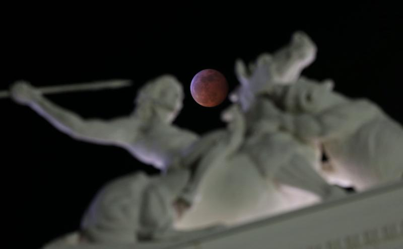 The moon is framed by a statue on the state Capitol during the total lunar eclipse Jan. 20 in Sacramento, California.