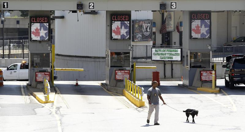 FILE - In this July 12, 2012, file photo a dog is used by authorities to investigate a bomb threat at the Detroit Windsor Tunnel Thursday, July 12, 2012. The temporary closing of the bridge is the result of a bomb threat, one of three recently in the Detroit area. (AP Photo/Paul Sancya)