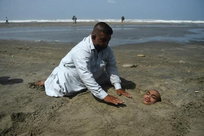A man buries his paralysed son in sand on a beach in Karachi during the eclipse. Folklore has it if the eclipse passes over them they will be cured (AFP Photo/Rizwan TABASSUM)