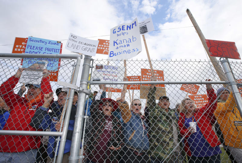 Protesters hold signs and chant behind a security fence as U.S. Secretary of the Interior Ryan Zinke arrives at Kanab Airport for departure on May 10, 2017, in Kanab, Utah. (George Frey/Getty Images)
