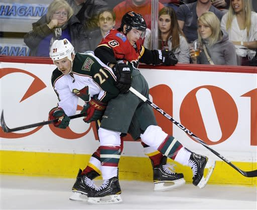 Minnesota Wild's' Kyle Brodziak, left, hits Calgary Flames' Brendan Morrison during third period NHL action in Calgary, Alberta, Tuesday Dec. 20, 2011. (AP Photo/The Canadian Press, Larry MacDougal)