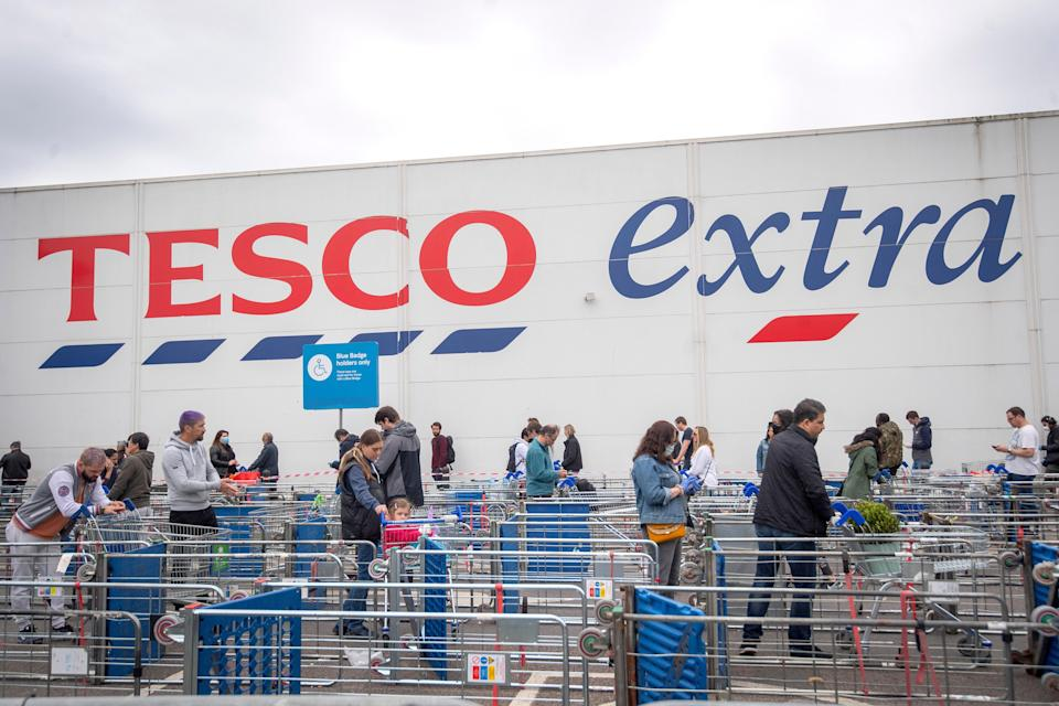 Customers queue outside a Tesco Extra store (PA Archive)