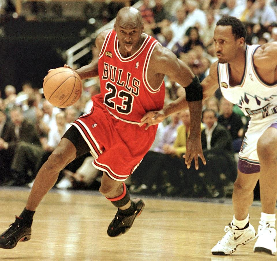 SALT LAKE CITY, UNITED STATES:  Michael Jordan (L) of the Chicago Bulls goes to the basket past Shandon Anderson of the Utah Jazz 14 June during game six of the NBA Finals at the Delta Center in Salt Lake City, UT. The Bulls lead the best-of-seven series 3-2.        AFP PHOTO/Mike NELSON (Photo credit should read MIKE NELSON/AFP via Getty Images)
