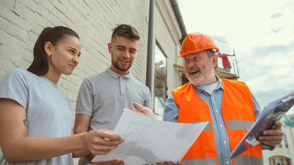 contractor talks with clients of new home