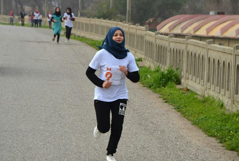 Iraqi women take part in a symbolic 900-metre marathon on March 8, 2018, to mark International Women's Day in Mosul, eight months after Iraqi forces retook the northern city from Islamic State group jihadists
