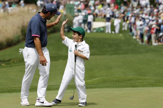 Francesco Molinari of Italy slaps hands with his son Tomasso during the par 3 contest held on the final day of practice for the 2018 Masters golf tournament at Augusta National Golf Club in Augusta, Georgia, U.S. April 4, 2018. REUTERS/Jonathan Ernst