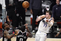 Dallas Mavericks guard Luka Doncic, right, passes the ball over Los Angeles Clippers forward Kawhi Leonard, left, and forward Marcus Morris Sr. during the second half in Game 5 of an NBA basketball first-round playoff series Wednesday, June 2, 2021, in Los Angeles. (AP Photo/Mark J. Terrill)