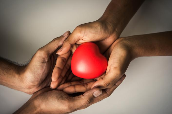 Helping hand of heart donor for patient in heart disease. Man give red heart to woman as couple. People lifestyle and couple romance. Healthcare and hospital medical concept. Symbolic of Valentine day