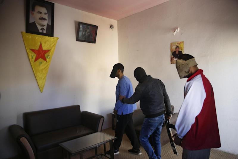 A Kurdish security officer, center, walks Alexanda Amon Kotey, left, and El Shafee Elsheikh to seats for a media interview (AP)