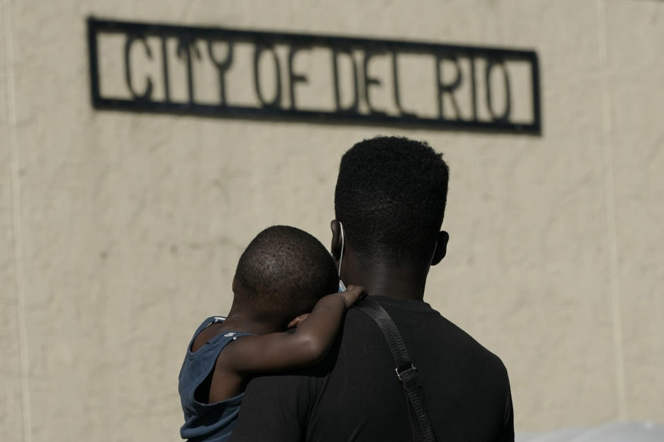 """A Haitian migrant carries a boy while waiting to board a bus provided by a humanitarian group after being released from U.S. Customs and Border Protection custody, Friday, Sept. 24, 2021, in Del Rio, Texas. The """"amistad,"""" or friendship, that Del Rio, Texas, and Ciudad Acuña, Mexico, celebrate with a festival each year has been important in helping them deal with the challenges from a migrant camp that shut down the border bridge between the two communities for more than a week. Federal officials announced the border crossing would reopen to passenger traffic late Saturday afternoon and to cargo traffic on Monday. (AP Photo/Julio Cortez)"""