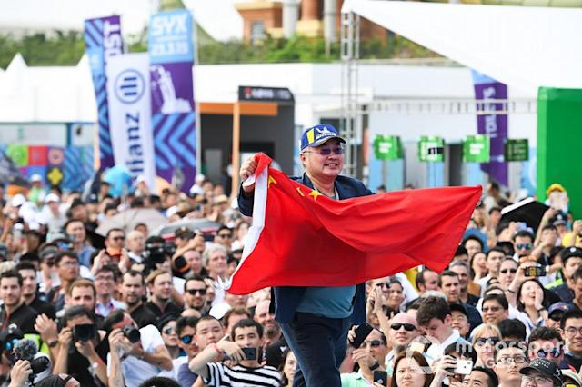 """A DS TECHEETAH representative on the podium with a flag of the People's Republic of China <span class=""""copyright"""">Sam Bagnall / Motorsport Images</span>"""