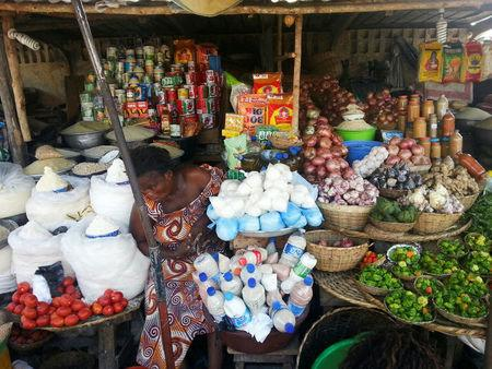 A woman sits in her market stall in Cotonou, Benin amid piles of merchandise