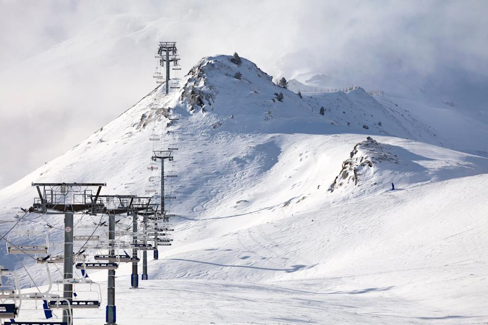 Empty ski lift heading toward the top of the snow-capped mountain lost in the cloud. (Photo: Gwengoat via Getty Images)